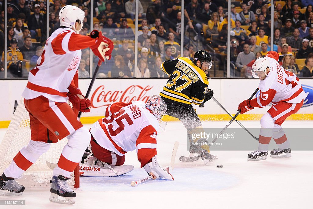 <a gi-track='captionPersonalityLinkClicked' href=/galleries/search?phrase=Patrice+Bergeron&family=editorial&specificpeople=204162 ng-click='$event.stopPropagation()'>Patrice Bergeron</a> #37 of the Boston Bruins tries to handle the puck against <a gi-track='captionPersonalityLinkClicked' href=/galleries/search?phrase=Jimmy+Howard&family=editorial&specificpeople=2118637 ng-click='$event.stopPropagation()'>Jimmy Howard</a> #35 and <a gi-track='captionPersonalityLinkClicked' href=/galleries/search?phrase=Pavel+Datsyuk&family=editorial&specificpeople=202893 ng-click='$event.stopPropagation()'>Pavel Datsyuk</a> #13 of the Detroit Red Wings at the TD Garden on October 5, 2013 in Boston, Massachusetts.