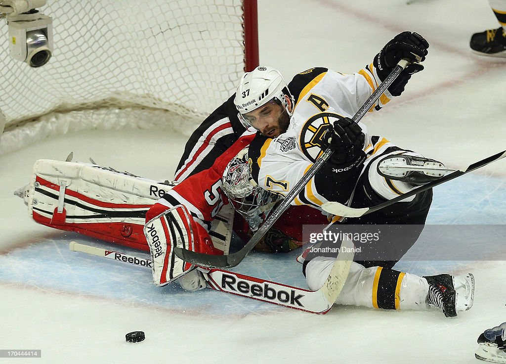 <a gi-track='captionPersonalityLinkClicked' href=/galleries/search?phrase=Patrice+Bergeron&family=editorial&specificpeople=204162 ng-click='$event.stopPropagation()'>Patrice Bergeron</a> #37 of the Boston Bruins tries to shoot against <a gi-track='captionPersonalityLinkClicked' href=/galleries/search?phrase=Corey+Crawford&family=editorial&specificpeople=818935 ng-click='$event.stopPropagation()'>Corey Crawford</a> #50 of the Chicago Blackhawks during Game One of the 2013 NHL Stanley Cup Finals at United Center on June 12, 2013 in Chicago, Illinois. The Blackhawks defeated the Bruins 4-3 in 3 overtimes.