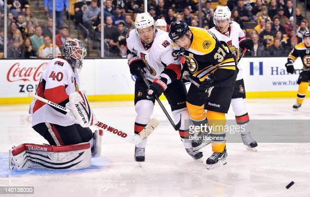 Patrice Bergeron of the Boston Bruins watches the loose puck against Milan Michalek of the Ottawa Senators at the TD Garden on February 28 2012 in...