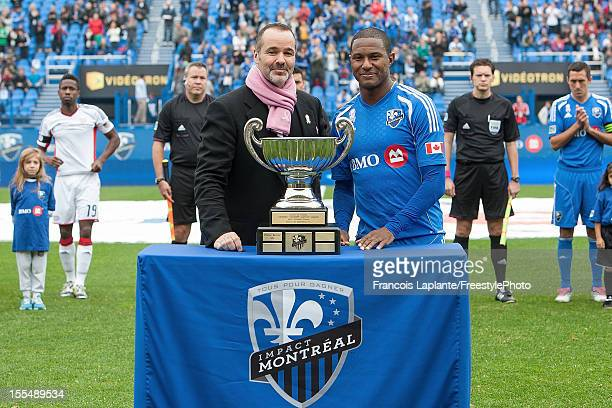 Patrice Bernier of the Montreal Impact receives the MVP trophy and poses for a photo along with team owner Joey Saputo prior to the MLS match against...