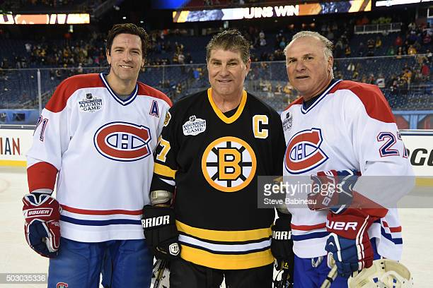 Patrice Brisebois and Lucien Deblois of the Montreal Canadiens pose with Ray Bourque of the Boston Bruins after the alumni game December 31 2015...