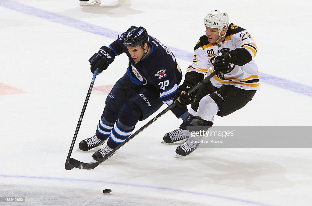 Patrice Cormier #28 of the Winnipeg Jets holds off Shawn Thornton #22 of the Boston Bruins as they chase the loose puck during third period action at the MTS Centre on April 10, 2014 in Winnipeg, Manitoba, Canada.