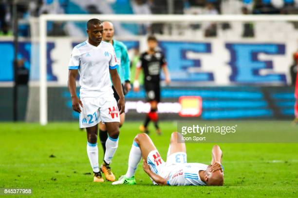 Patrice Evra and Aymen Abdennour of Marseille is injured during the Ligue 1 match between Olympique Marseille and Stade Rennais at Stade Velodrome on...