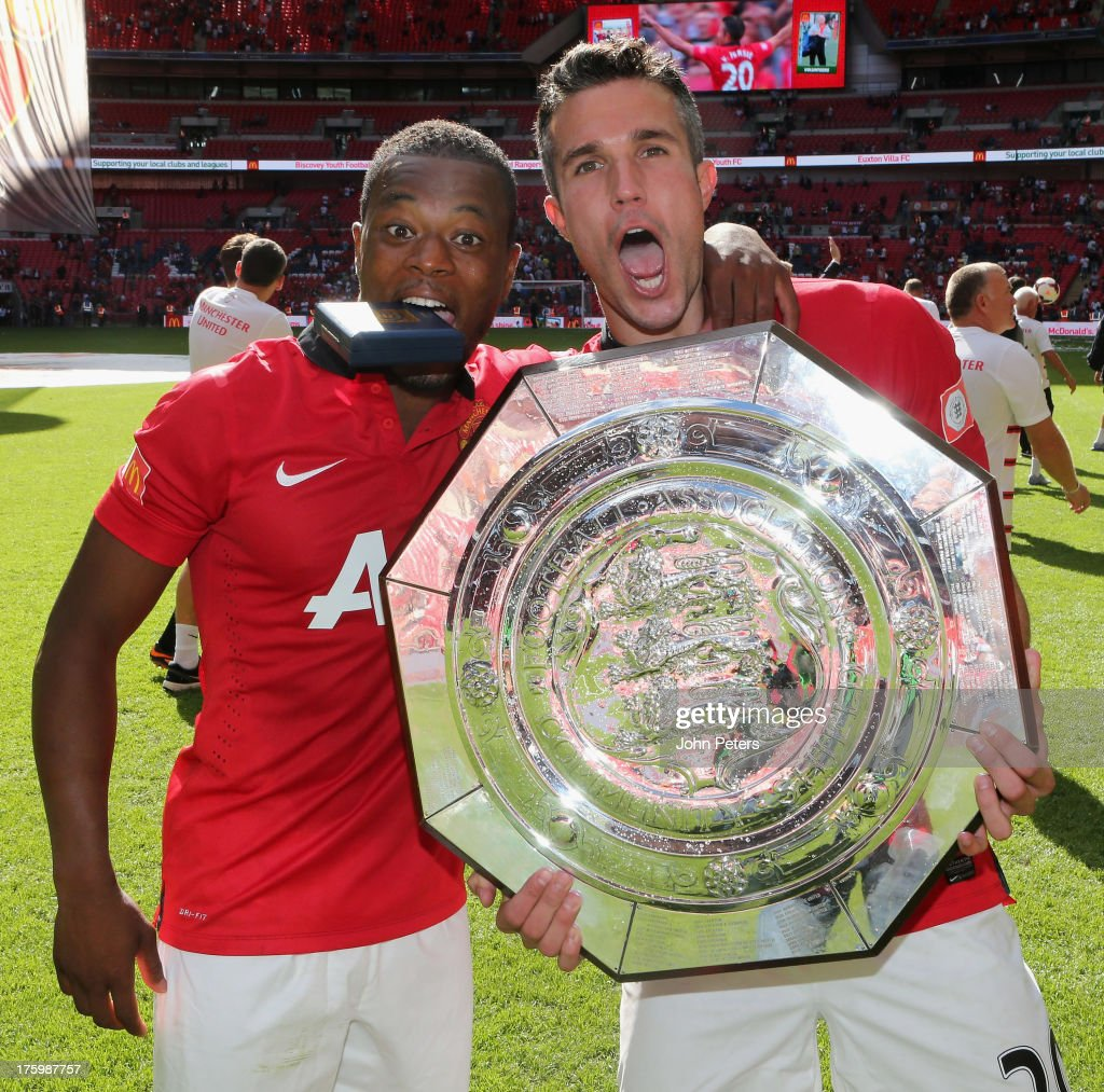 <a gi-track='captionPersonalityLinkClicked' href=/galleries/search?phrase=Patrice+Evra&family=editorial&specificpeople=714865 ng-click='$event.stopPropagation()'>Patrice Evra</a> and Robin van Persie of Manchester United pose with the FA Community Shield trophy after the FA Community Shield match between Manchester United and Wigan Athletic at Wembley Stadium on August 11, 2013 in London, England.
