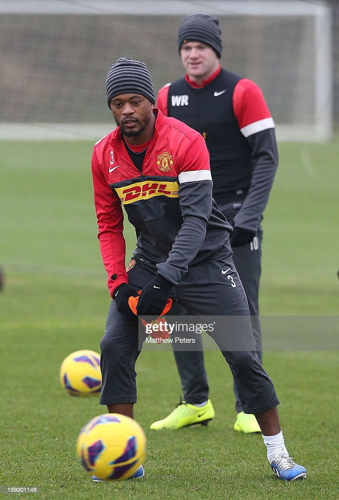 Patrice Evra (L) and Wayne Rooney of Manchester United in action during a first team training session at Carrington Training Ground on January 11, 2013 in Manchester, England.
