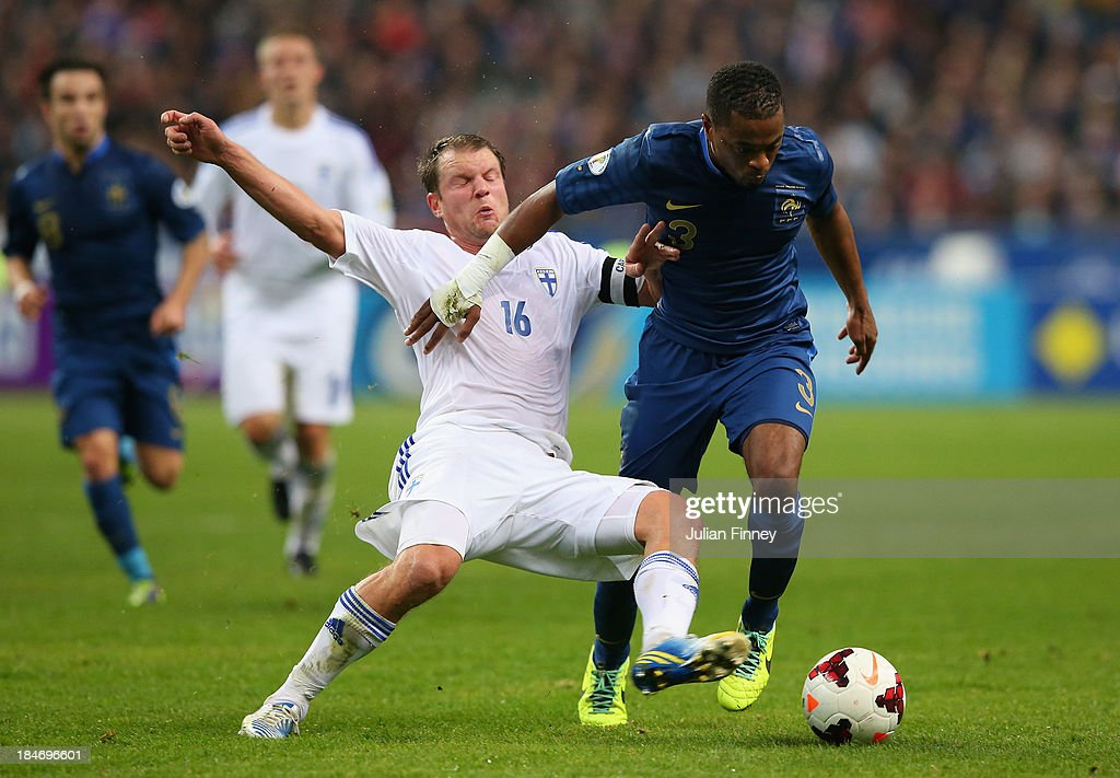 Patrice Evra of France battles with Teemu Tainio of Finland during the FIFA 2014 World Cup Qualifying Group I match between France and Finland at the Stade de France on October 15, 2013 in Paris, France.