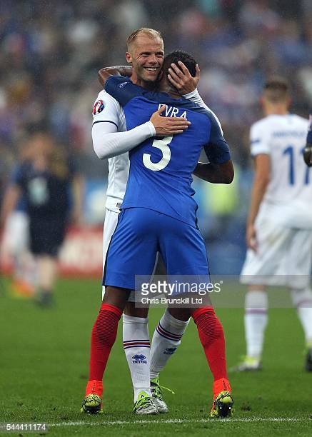 Patrice Evra of France embraces Eidur Gudjohnsen of Iceland at fulltime following the UEFA Euro 2016 Quarter Final match between France and Iceland...