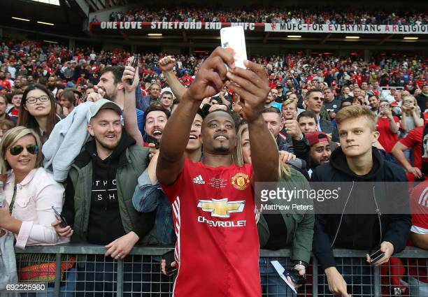 Patrice Evra of Manchester United '08 XI takes a selfie with fans after the Michael Carrick Testimonial match between Manchester United '08 XI and...