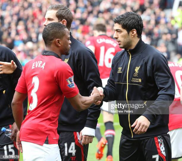 Patrice Evra of Manchester United and Luis Suarez of Liverpool shakes hands ahead of the Barclays Premier League match between Manchester United and...