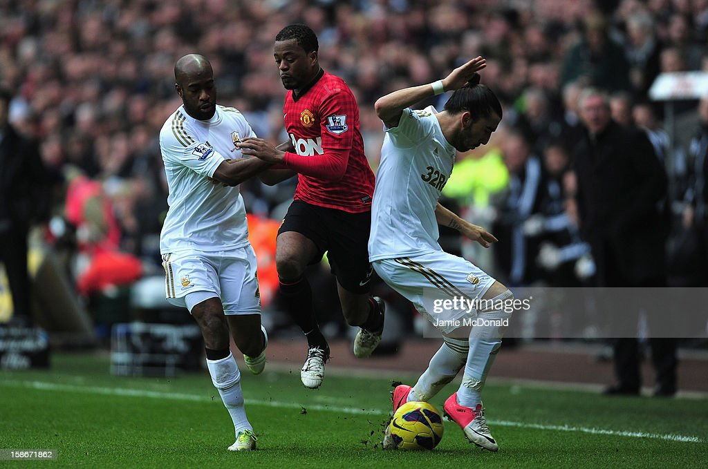 Patrice Evra of Manchester United battles with Chico Flores and Nathan Dyer of Swansea City during the Barclays Premier League match between Swansea...