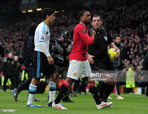 Patrice Evra of Manchester United celebrates victory as he walks off with Luis Suarez of Liverpool during the Barclays Premier League match between...