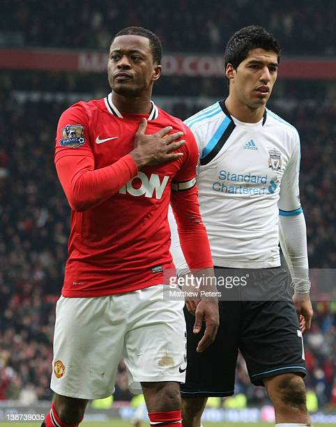 Patrice Evra of Manchester United celebrates while Luis Suarez of Liverpool walks off after the Barclays Premier League match between Manchester...