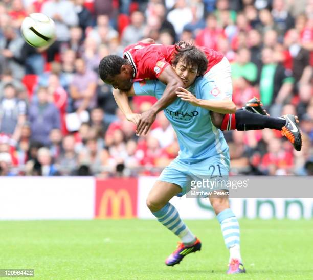 Patrice Evra of Manchester United clashes with David Silva of Manchester City during the FA Community Shield match between Manchester City and...