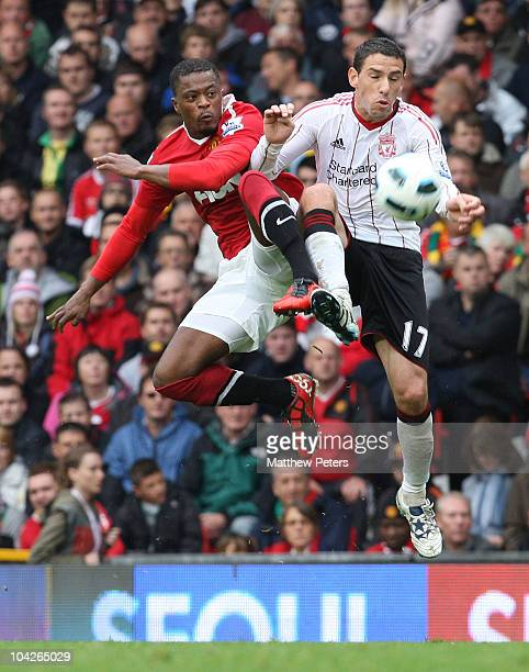 Patrice Evra of Manchester United clashes with Maxi Rodriguez of Liverpool during the Barclays Premier League match between Manchester United and...