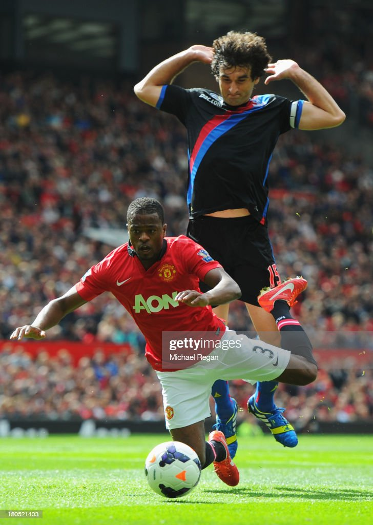 Patrice Evra of Manchester United goes to ground under a challenge by Mile Jedinak of Crystal Palace during the Barclays Premier League match between Manchester United and Crystal Palace at Old Trafford on September 14, 2013 in Manchester, England.