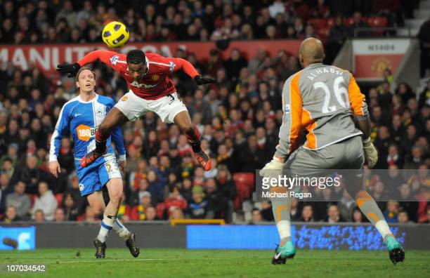 Patrice Evra of Manchester United heads the ball past Wigan's goalkeeper Ali Al Habsi to score the opening goal during the Barclays Premier League...