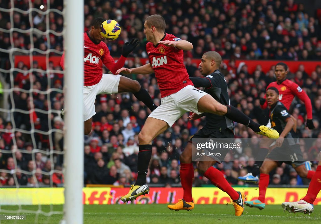 Patrice Evra of Manchester United heads the ball which deflected off team-mate Nemanja Vidic for the second goal during the Barclays Premier League match between Manchester United and Liverpool at Old Trafford on January 13, 2013 in Manchester, England.