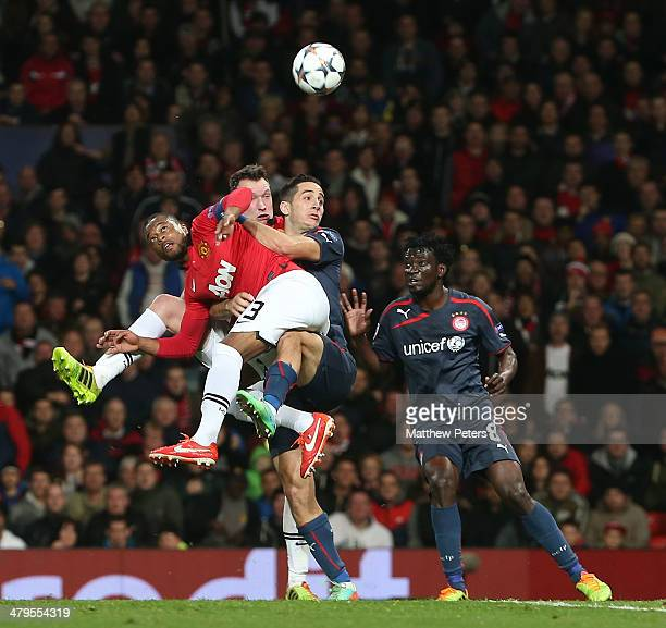 Patrice Evra of Manchester United in action with Kostas Manolas of Olympiacos FC during the UEFA Champions League Round of 16 second leg match...
