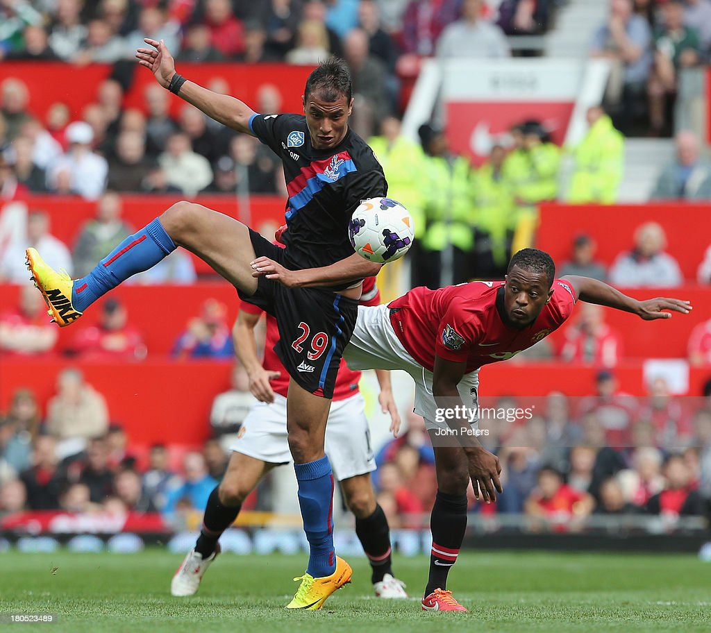Patrice Evra of Manchester United in action with Marouane Chamakh of Crystal Palace during the Barclays Premier League match between Manchester United and Crystal Palace at Old Trafford on September 14, 2013 in Manchester, England.