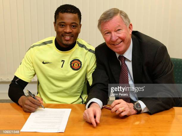 Patrice Evra of Manchester United poses with Sir Alex Ferguson after signing a new contract with Manchester United at Carrington Training Ground on...