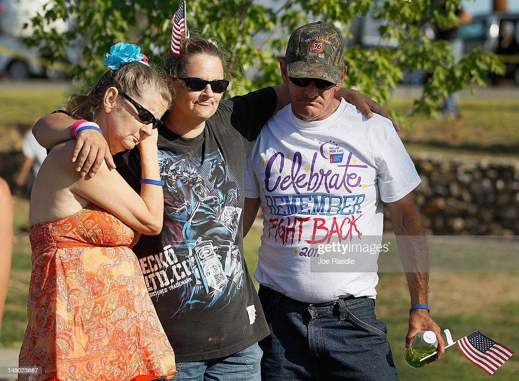 Patrice Landon, Annie Philliber and Tim Landon (L-R) hug in Cunningham Park during a moment of silence at 5:41 p.m. which was when the monstrous tornado first hit the city a year ago to the day on May 22, 2012 in Joplin, Missouri. The EF-5 tornado devastated the area leaving behind a path of destruction along with 161 deaths and hundreds of injuries, but one year later there are signs that the town is beginning to recover.