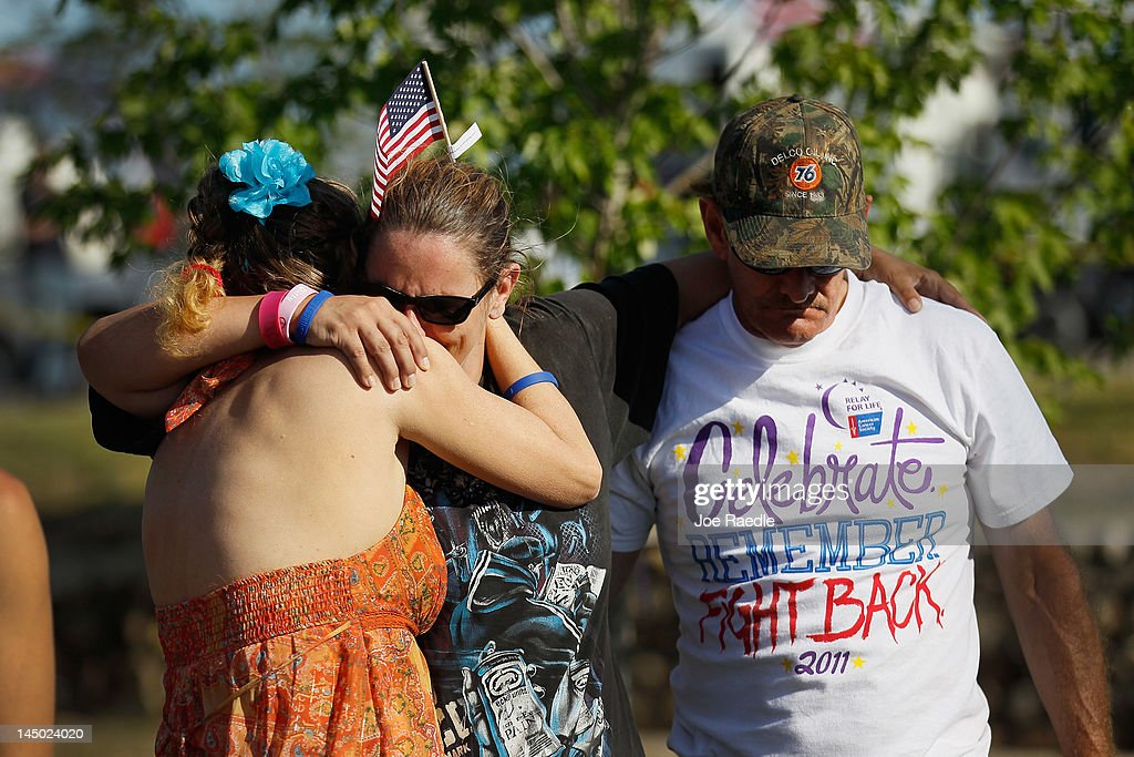 Patrice Landon, Annie Philliber and Tim Landon hug in Cunningham Park during a moment of silence at 5:41 p.m. which was when the monstrous tornado first hit the city a year ago to the day on May 22, 2012 in Joplin, Missouri. The EF-5 tornado devastated the area leaving behind a path of destruction along with 161 deaths and hundreds of injuries, but one year later there are signs that the town is beginning to recover.