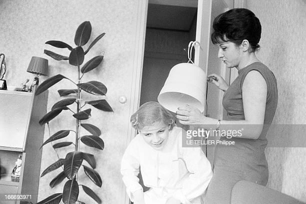 Patricia Gozzi Portrait de la jeune actrice Patricia GOZZI s'installant sous un casque de sèchecheveux tenu par une jeune femme brune debout à droite