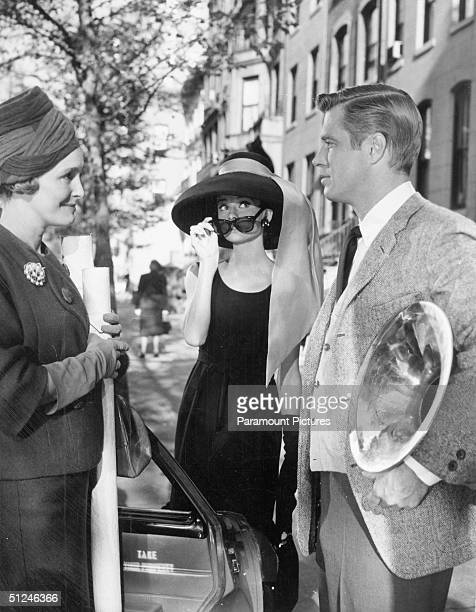 1961 Patricia Neal converses with George Peppard as Audrey Hepburn peers over her sunglasses in a still from director Blake Edwards' film 'Breakfast...