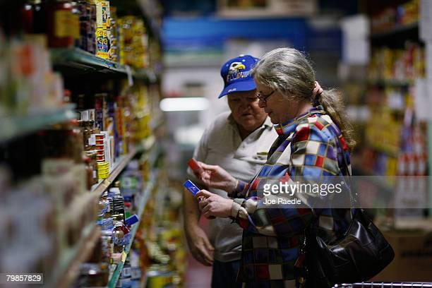 Patricia Russell and Ralph Ashley shop for groceries at Lorenzo's Supermarket as a new government report showed that consumer prices rose last month...