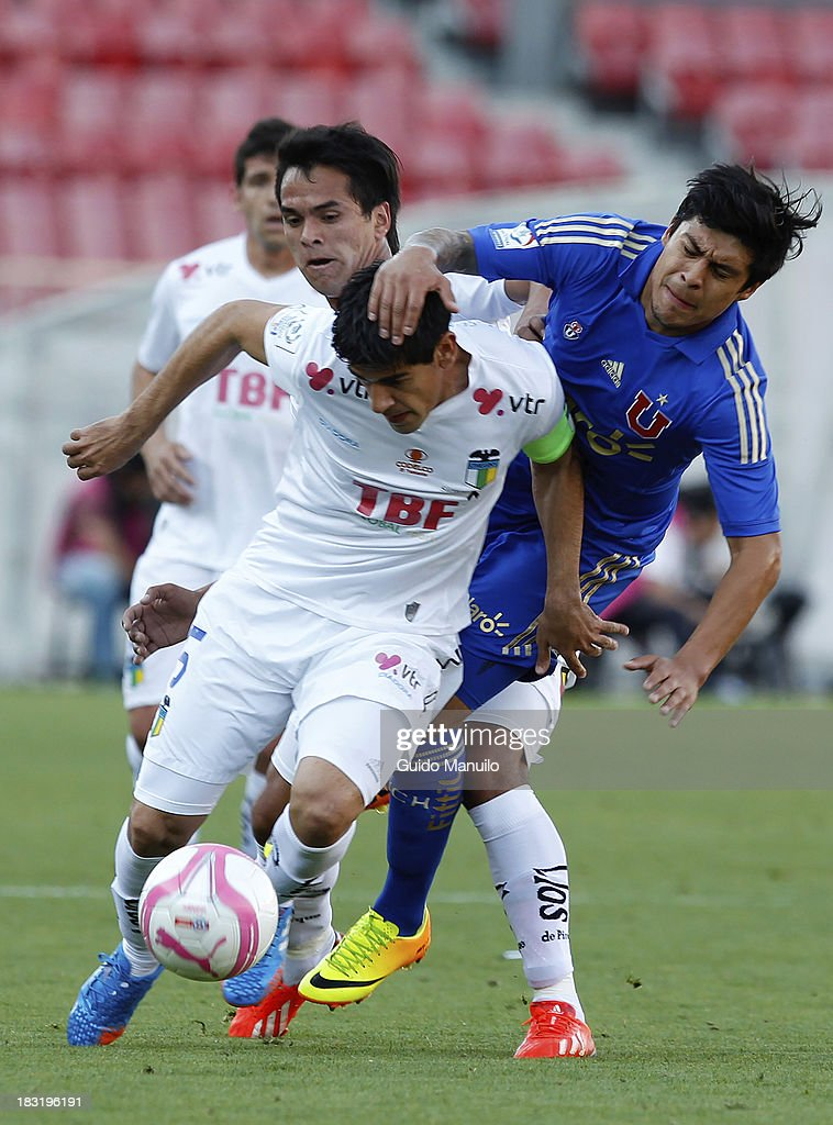 Patricio Rubio of U de Chile fights for the ball with Julio Barroso during a match between O'Higgins and U de Chile as part of the Torneo Apertura at National Stadium, on October 05, 2013 in Santiago, Chile.