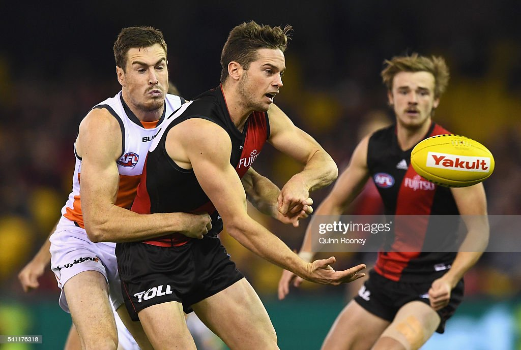 Patrick Ambrose of the Bombers handballs whilst being tackled by Jeremy Cameron of the Giants during the round 13 AFL match between the Essendon...