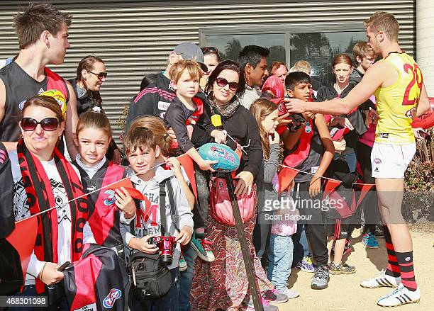 Patrick Ambrose of the Bombers poses for photographs and signs autographs with supporters in the crowd who turned up to watch training after an...