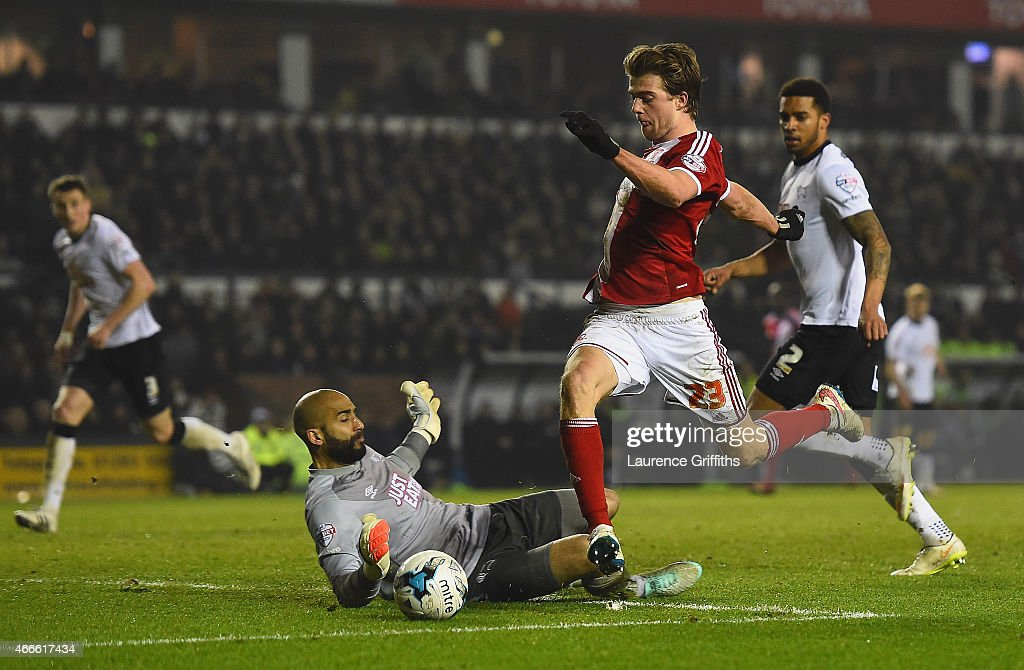 Patrick Bamford of Middlesbrough rounds goalkeeper Lee Grant of Derby to score opening goal during the Sky Bet Championship match between Derby County and Middlesbrough at iPro Stadium on March 17, 2015 in Derby, England.
