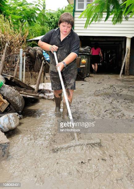 Patrick Barnes sweeps out mud from his home as flood waters fall on January 16 2011 in Rockhampton Australia Rockampton experienced some of...