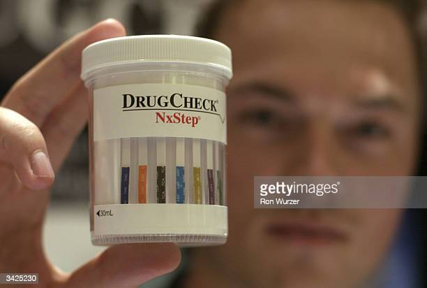 Patrick Beentjes of Scienta int'l inc holds up urine container to be used for a drug test at the Drug Alcohol Testing Industry Association annual...