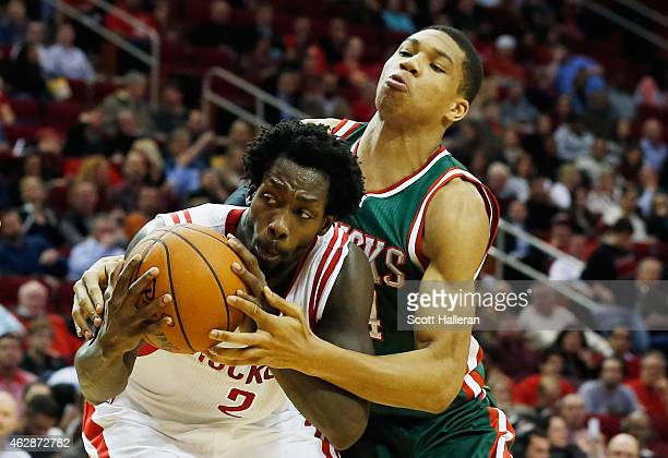 Patrick Beverley of the Houston Rockets battles for a rebound with Giannis Antetokounmpo of the Milwaukee Bucks during their game at the Toyota...
