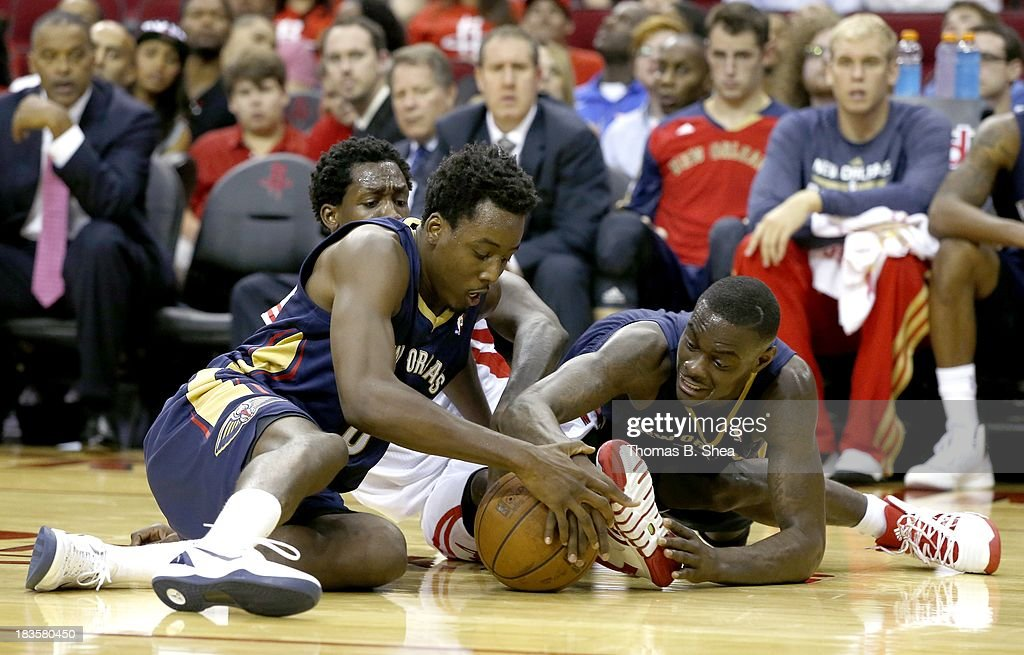 Patrick Beverley #2 of the Houston Rockets fights for a loose ball against Al-Farouq Aminu #0 and Anthony Morrow #3 of the New Orleans Pelicans in a preseason NBA game on October 5, 2013 at Toyota Center in Houston, Texas. The Pelicans won 116 to 115.