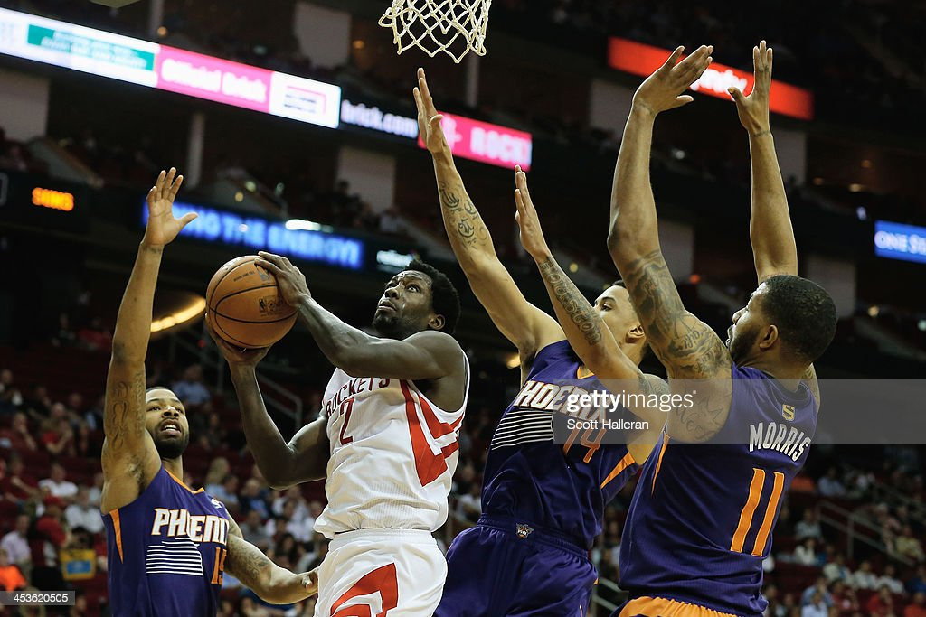 Patrick Beverley #2 of the Houston Rockets takes a shot as he is defended by Marcus Morris, Gerald Green #14 and Markieff Morris #11 of the Phoenix Suns at Toyota Center on December 4, 2013 in Houston, Texas.
