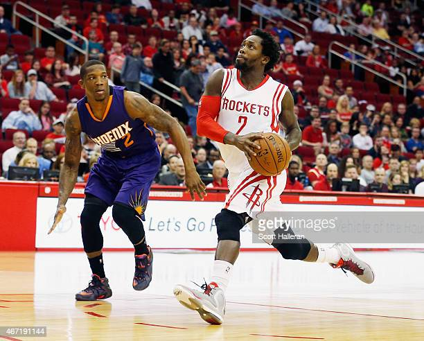 Patrick Beverley of the Houston Rockets takes the basketball up the court in front of Eric Bledsoe of the Phoenix Suns during their game against the...