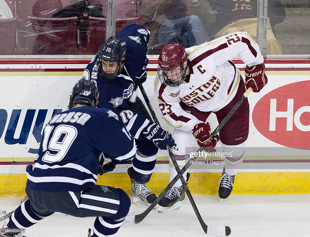 Patrick Brown #23 of the Boston College Eagles battles against Jeff Silengo #18 of the New Hampshire Wildcats during NCAA hockey action at Kelley Rink on December 6, 2013 in Chestnut Hill, Massachusetts.