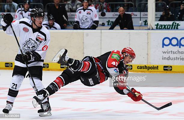 Patrick Buzas challenges Christopher Minard of Koeln during the DEL match between Koelner Haie and Thomas Sabo Ice Tigers at Lanxess Arena on...