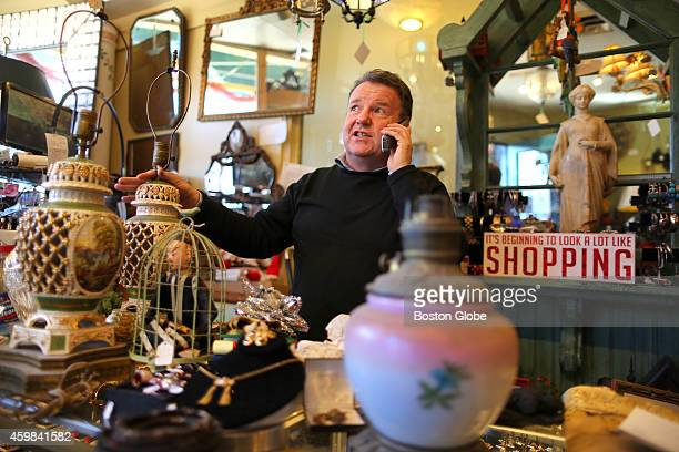 Patrick Byrne coowner of Cob Webs antique store on Centre Street chats with a customer on the phone Shoppers and store owners welcomed Small Business...