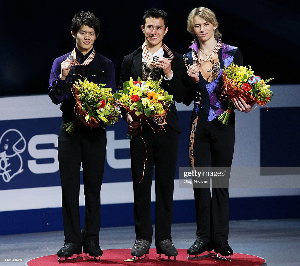 <a gi-track='captionPersonalityLinkClicked' href=/galleries/search?phrase=Patrick+Chan&family=editorial&specificpeople=4036503 ng-click='$event.stopPropagation()'>Patrick Chan</a> of Canada (C) smiles on the podium near <a gi-track='captionPersonalityLinkClicked' href=/galleries/search?phrase=Takahiko+Kozuka&family=editorial&specificpeople=686867 ng-click='$event.stopPropagation()'>Takahiko Kozuka</a> of Japan (L) and Artur Gachinski of Russia after winning the men's event of the ISU World Figure Skating Championships at Megasport Ice Rink on April 28, 2011 in Moscow, Russia.