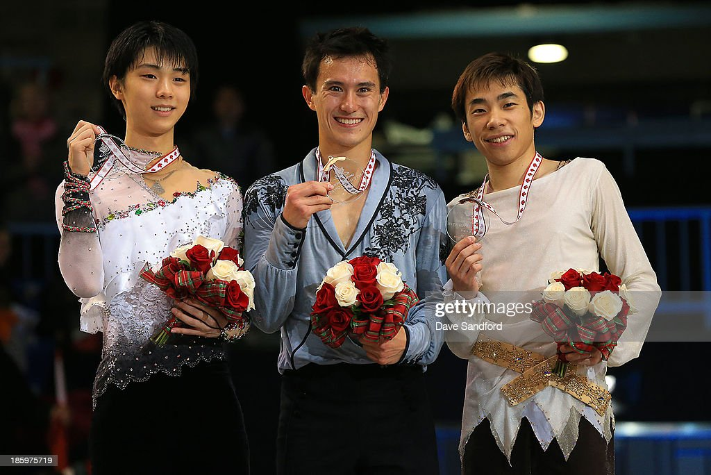 <a gi-track='captionPersonalityLinkClicked' href=/galleries/search?phrase=Patrick+Chan&family=editorial&specificpeople=4036503 ng-click='$event.stopPropagation()'>Patrick Chan</a> (C) of Canada with the gold medal celebrates on the podium with silver medalist Yuzuru Hanyu (L) of Japan and bronze medalist <a gi-track='captionPersonalityLinkClicked' href=/galleries/search?phrase=Nobunari+Oda+-+Figure+Skater&family=editorial&specificpeople=727292 ng-click='$event.stopPropagation()'>Nobunari Oda</a> of Japan during the men's free program on day two at the ISU GP 2013 Skate Canada International at Harbour Station on October 26, 2013 in Saint John, New Brunswick, Canada.