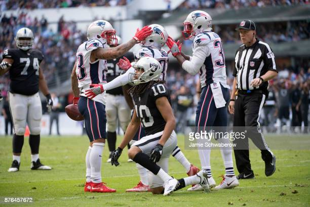 Patrick Chung Jonathan Jones and Duron Harmon of the New England Patriots celebrate after stripping the ball from Seth Roberts of the Oakland Raiders...