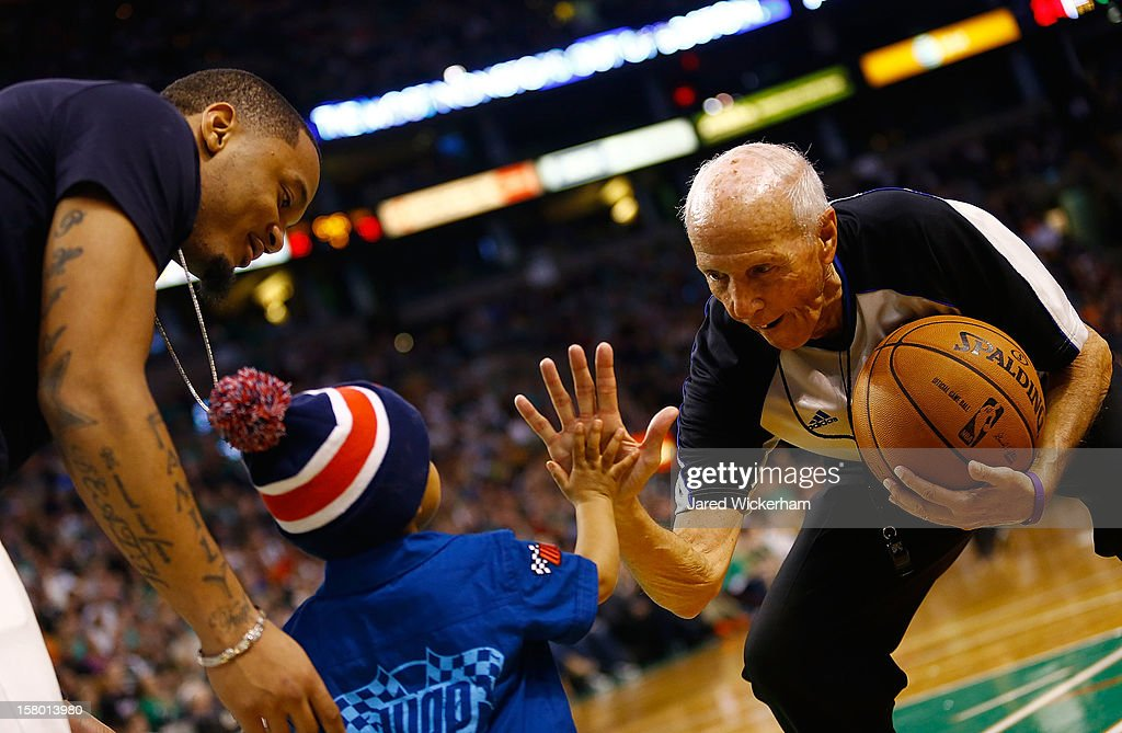Patrick Chung #27 of the New England Patriots, and his son Taj, high-five referee Dick Bavetta court side during the game between the Boston Celtics and the Philadelphia 76ers on December 8, 2012 at TD Garden in Boston, Massachusetts.