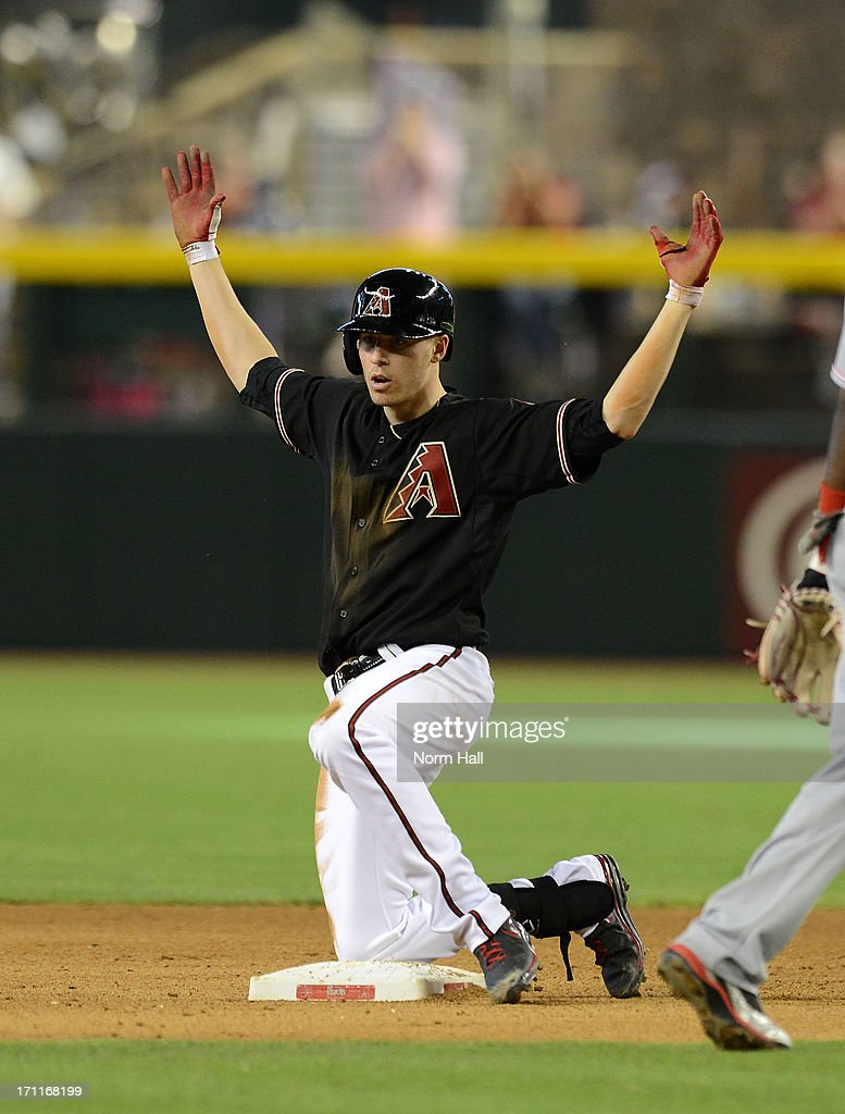 Patrick Corbin #46 of the Arizona Diamondbacks celebrates hitting a double while kneeling on second base against the Cincinnati Reds at Chase Field on June 22, 2013 in Phoenix, Arizona.