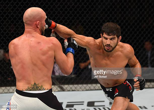 Patrick Cote punches Josh Burkman of the United States in their welterweight bout during the UFC event at the SaskTel Centre on August 23 2015 in...