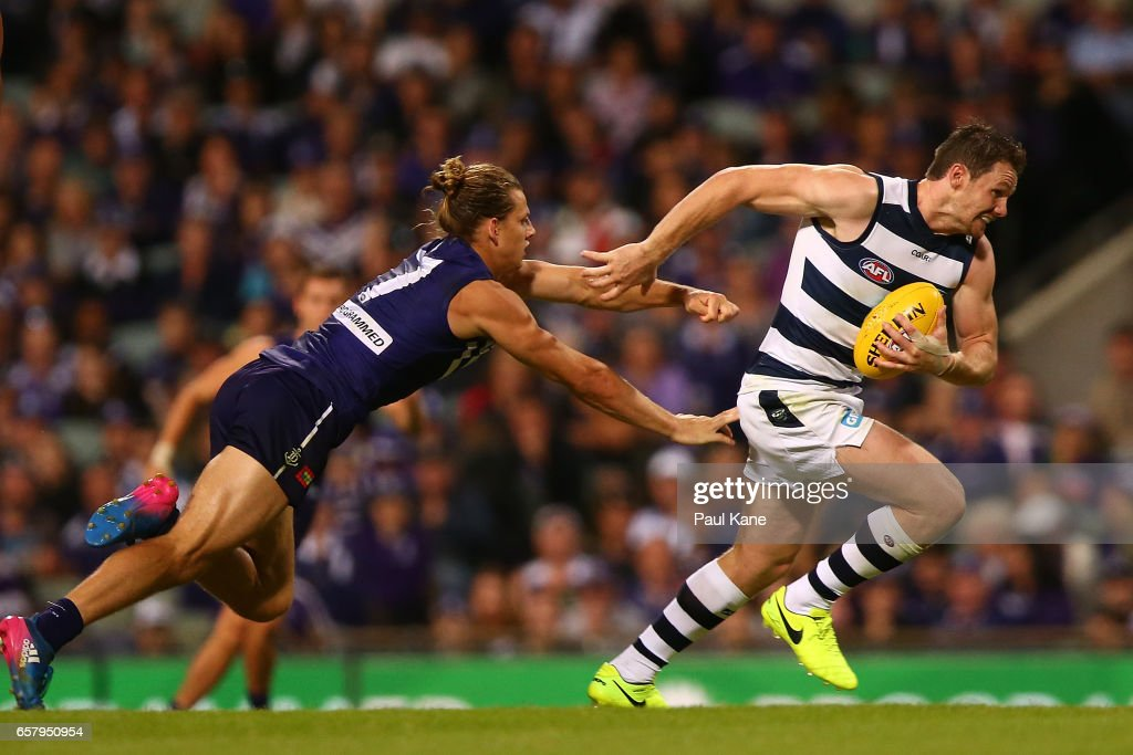 Patrick Dangerfield of the Cats breaks clear of a tackle by Nathan Fyfe of the Dockers during the round one AFL match between the Fremantle Dockers and the Geelong Cats at Domain Stadium on March 26, 2017 in Perth, Australia.