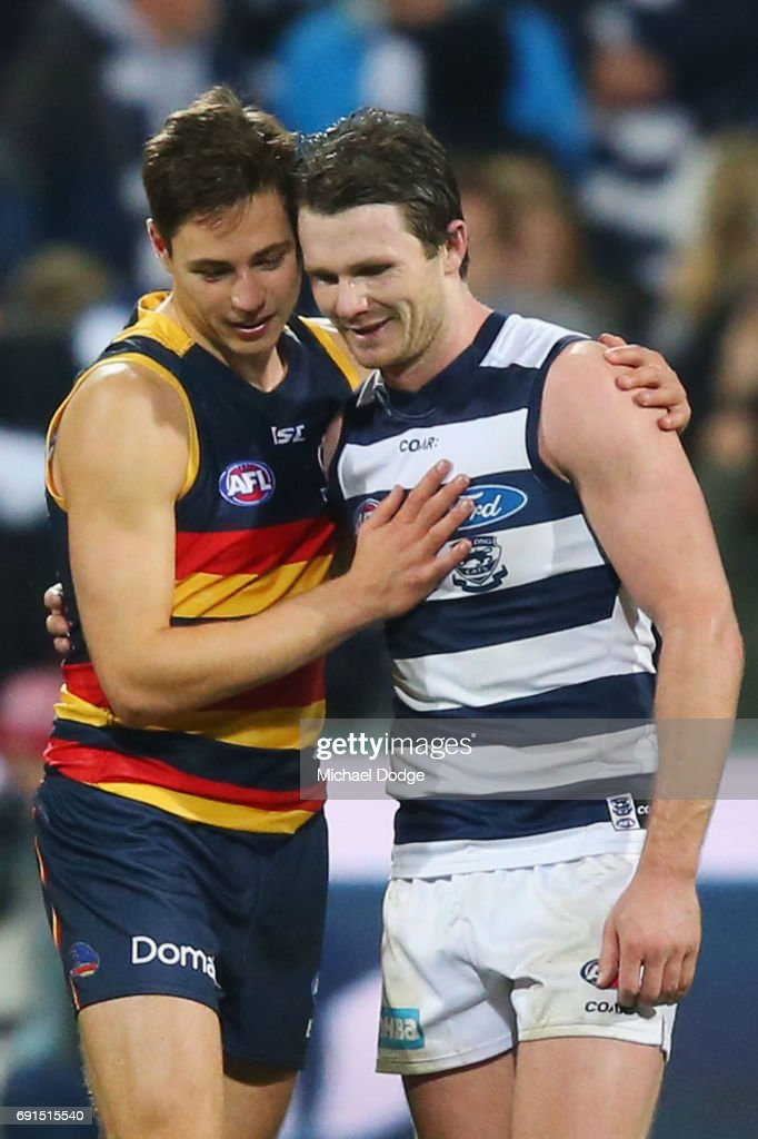 Patrick Dangerfield of the Cats (R) celebrates the win when catching up with former teammate Jake Lever of the Crows during the round 11 AFL match between the Geelong Cats and the Adelaide Crows at Simonds Stadium on June 2, 2017 in Geelong, Australia.
